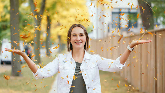 Young woman smiling and throwing autumn leaves in the air