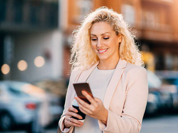 Smiling blond woman on the street looking on her mobile phone