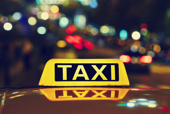 lighted taxi sign on a car roof