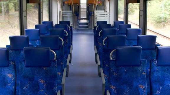 Inside of a train wagon with empty blue seats