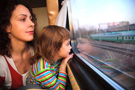 Young woman and a young girl are looking out of a train window