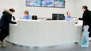 A service desk with two employees and two clients at each end