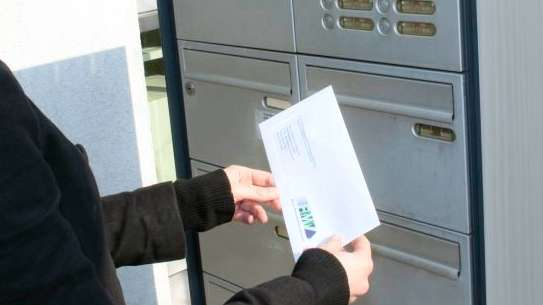 Woman inserting a letter into the letterbox