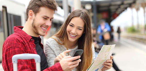 A young couple on the railway platform with a city map