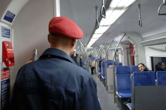 Man with red cap and blue uniform seen from behind in a suburban train