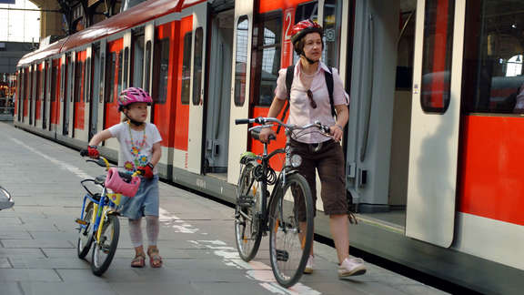Woman and a young girl with bikes on the platform next to a red train with opened doors