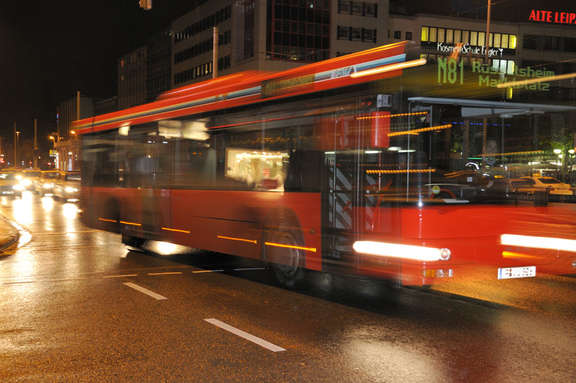 Red bus number N81 driving by night