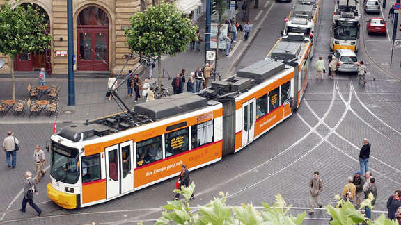 Orange and white tram turning around a corner seen from above