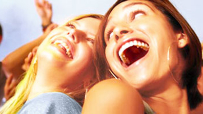 A blonde laughing woman leans her head back and next to her stands a brunette laughing woman back to back with her. They both look at each other. It seems as if they are at a party and are having a good time. In the background, there is a crowd of people celebrating as well.