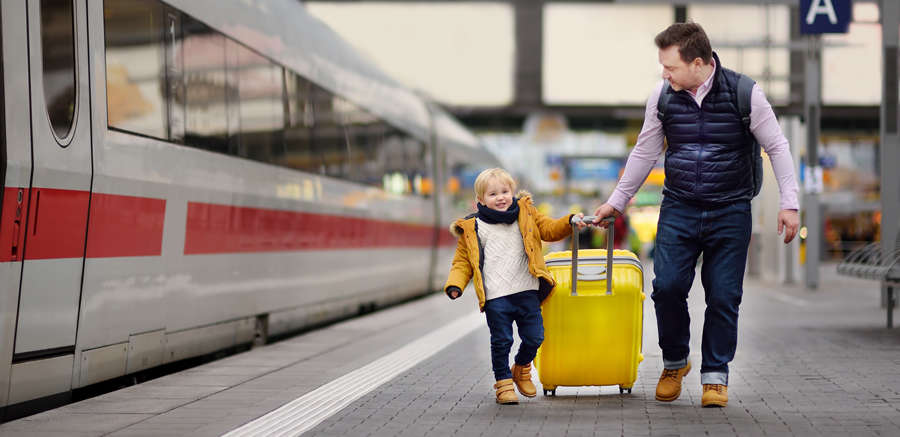 Father and son with suitcases on the platform